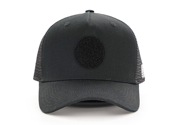 Front of All Black Trucker Hat With a Black Velcro Logo & a American Flag Logo on Side