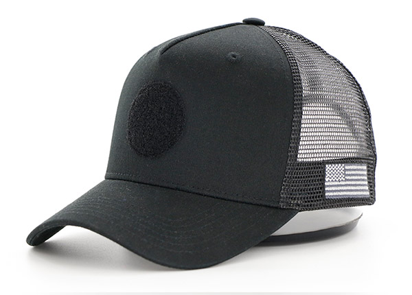 Slant of All Black Trucker Hat With a Black Velcro Logo & a American Flag Logo on Side