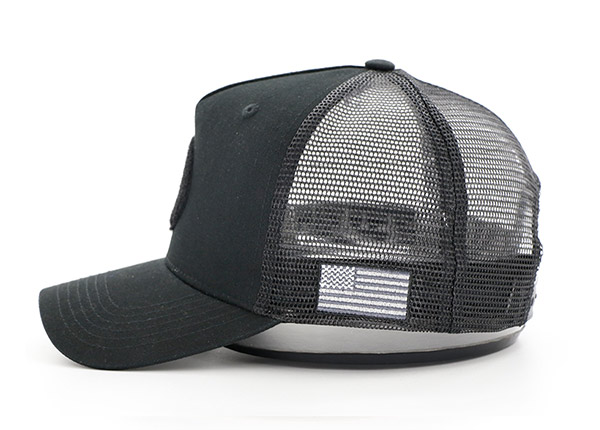 Side of All Black Trucker Hat With a Black Velcro Logo & a American Flag Logo on Side
