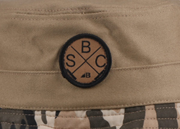 Logo of Fitted Washed Cotton Tan Bucket Hat with Camo Brim